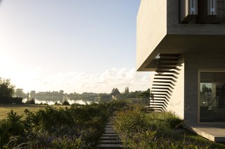 Lush landscaping anchors the home to its serene natural setting.