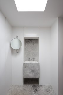 One of the home's six bathrooms strikes an elegant balance between white walls and quarried stone.