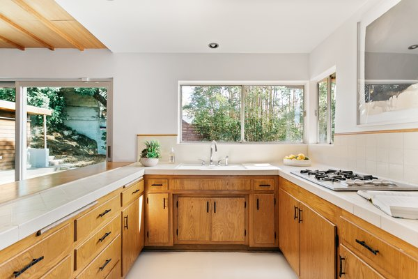 The U-shaped kitchen features vintage wood cabinetry and appliances. An open peninsula provides views into the dining and living rooms.