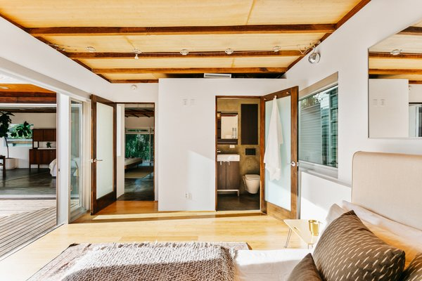 A peek at one of three bedrooms, which features large sliding doors that open directly to the outdoors and drench the room in natural light.