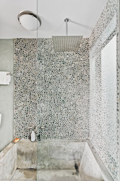 The second bathroom features a deep cast-concrete soaking tub and shower. A natural mosaic of pebbled stones line the shower walls.