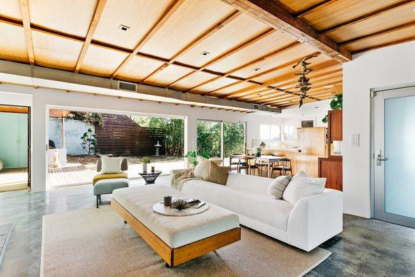 The main entrance opens to a large living room and a wall of glass that stretches along the entire space. Redwood beams and veneer line the ceiling, while stained concrete floors complement the earthy aesthetic.