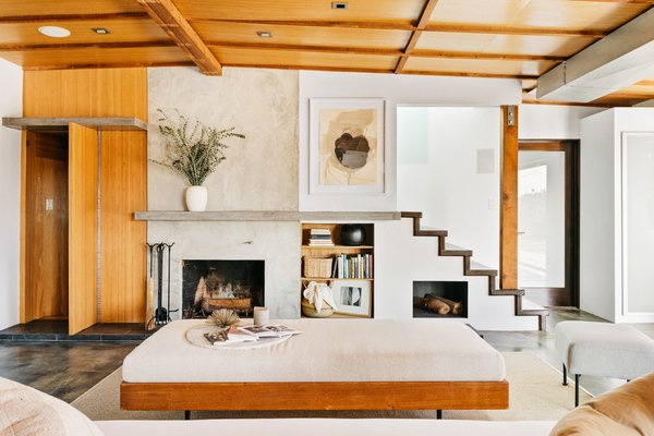 A focal point of the living area is the aesthetically pleasing fireplace wall, which elegantly mixes materials and features a mantel that runs across to meet the staircase tread. The open stairs lead up to an airy bedroom.
