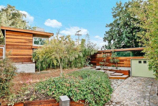 Originally built in 1937, the home has been modernized inside and out. A stone driveway ends at the one-car garage, while a cascade of steps lead up to the entryway courtyard.