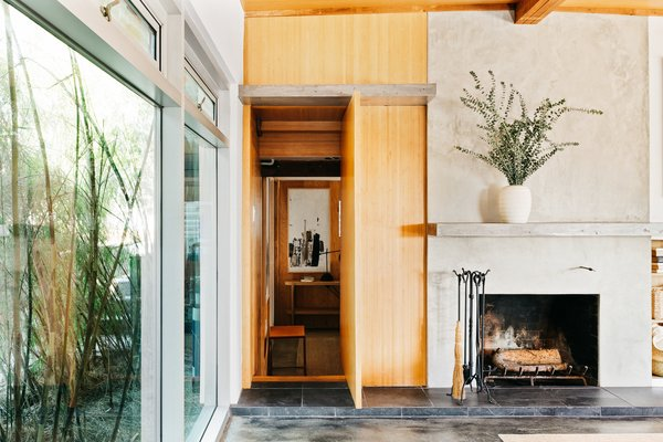 On the opposite side of the fireplace, a hidden door disguises the entrance to another bedroom.