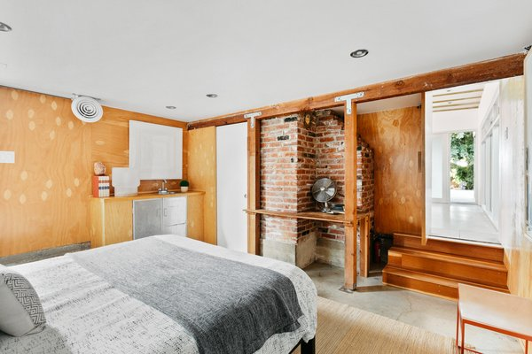 Beneath the bedroom is a hidden space off of the main living area. A few steps lead down to the large room, which is wrapped in plywood, exposed framing, and concrete floors.