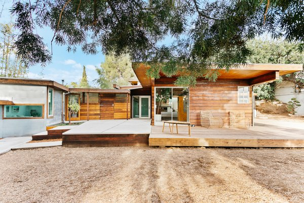 An additional concrete patio adjoins the deck near the main entrance, connecting with the detached studio and garage. Several large pines around the .20-acre lot offer a canopy to escape the sun.