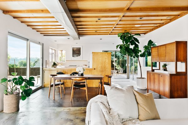 The living room flows into the dining area and kitchen, with each space differentiated by transitions in the flooring and ceiling. Sliding doors and windows wrap around the space to provide natural light and access to the home's multiple outdoor areas.
