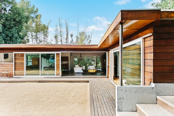 The deck continues around the other side of the home and traces the home's L-shaped floor plan. Expansive sliding doors in the living room and master bedroom provide a seamless transition between indoor and outdoor spaces.