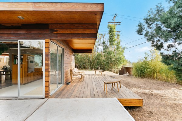 Outside, a wrap-around deck begins off the kitchen. A deep overhang provides some shade for the wide sliding doors that wrap around the corner of the home.