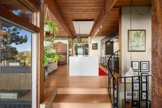 Several stairs lead up to the kitchen while a spiral staircase leads down to a covered patio area. The wooden beams draw the eye past the island to clerestory windows and sliding glass doors on the other side.
