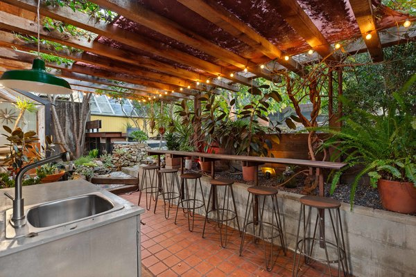 Another lush patio area just off the kitchen offers a pergola-topped outdoor kitchen and bar. Other features of the backyard include a fire pit, raised-bed gardens, and matured fruit trees.
