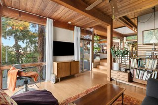 The classic post-and-beam style defines the home's interior. Exposed wood ceilings and lightly colored hardwood floors run throughout the open concept living area.