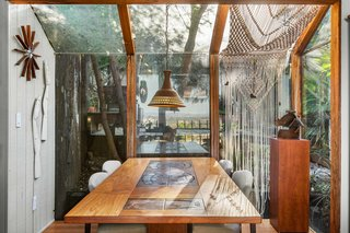A solarium-style corner protrudes into the rear garden, providing a unique spot for dining under the canopy of trees.