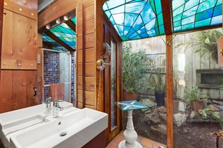 A wood-clad bathroom on the lower level features another solarium-like corner, topped with stained glass and surrounded by a private rock garden.