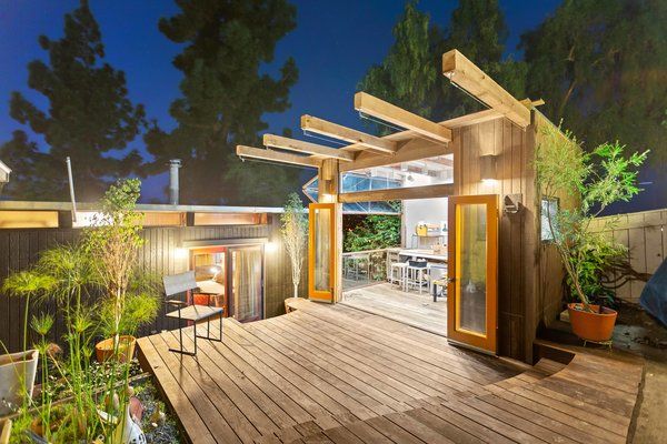 Lastly, a rooftop deck flanks an open-air studio. Designed to mimic the post-and-beam style, the unique workshop features accordion doors on one side and a custom-built, bi-fold garage door along another.