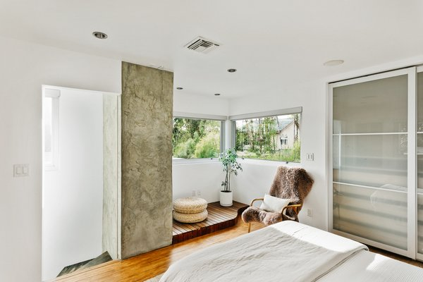 Upstairs, a bright bedroom features corner windows overlooking the front yard.