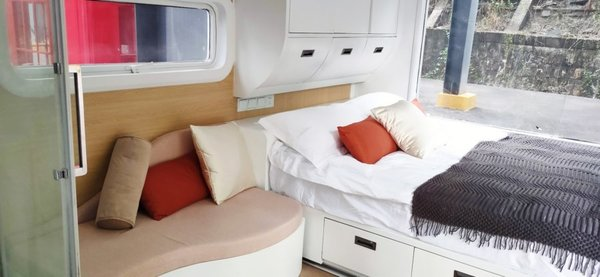 Next to the couch is a bed with built-in storage and a wardrobe. Aluminum alloy-framed windows grant one-way views of the outdoors.