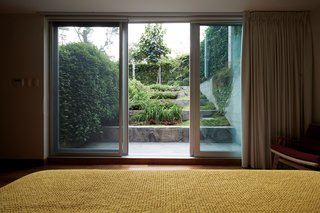 The sliding doors in the master bedroom open up to the garden and terrace.