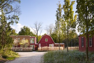 Vibrant red siding references the original buildings on the site.