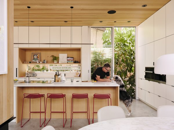 In the kitchen, a glass backsplash is one of many connections to the outdoors. The Hee barstools are by Hay and the Highline pendant light is by Rakumba Lighting Australia.