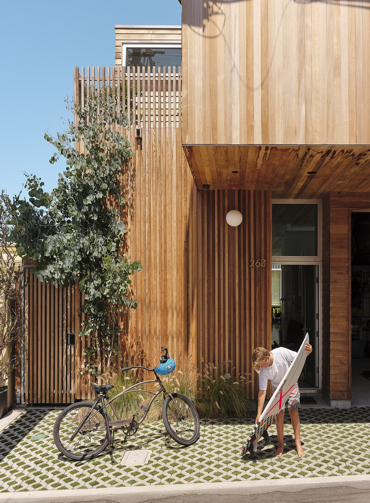 Doors, Swing Door Type, Exterior, and Wood The alley entrance is shaded by a cantilevered volume on the second floor. Turf-block pavers reduce runoff.  Photos from It Took a Neighborhood to Build This Beachside Bungalow