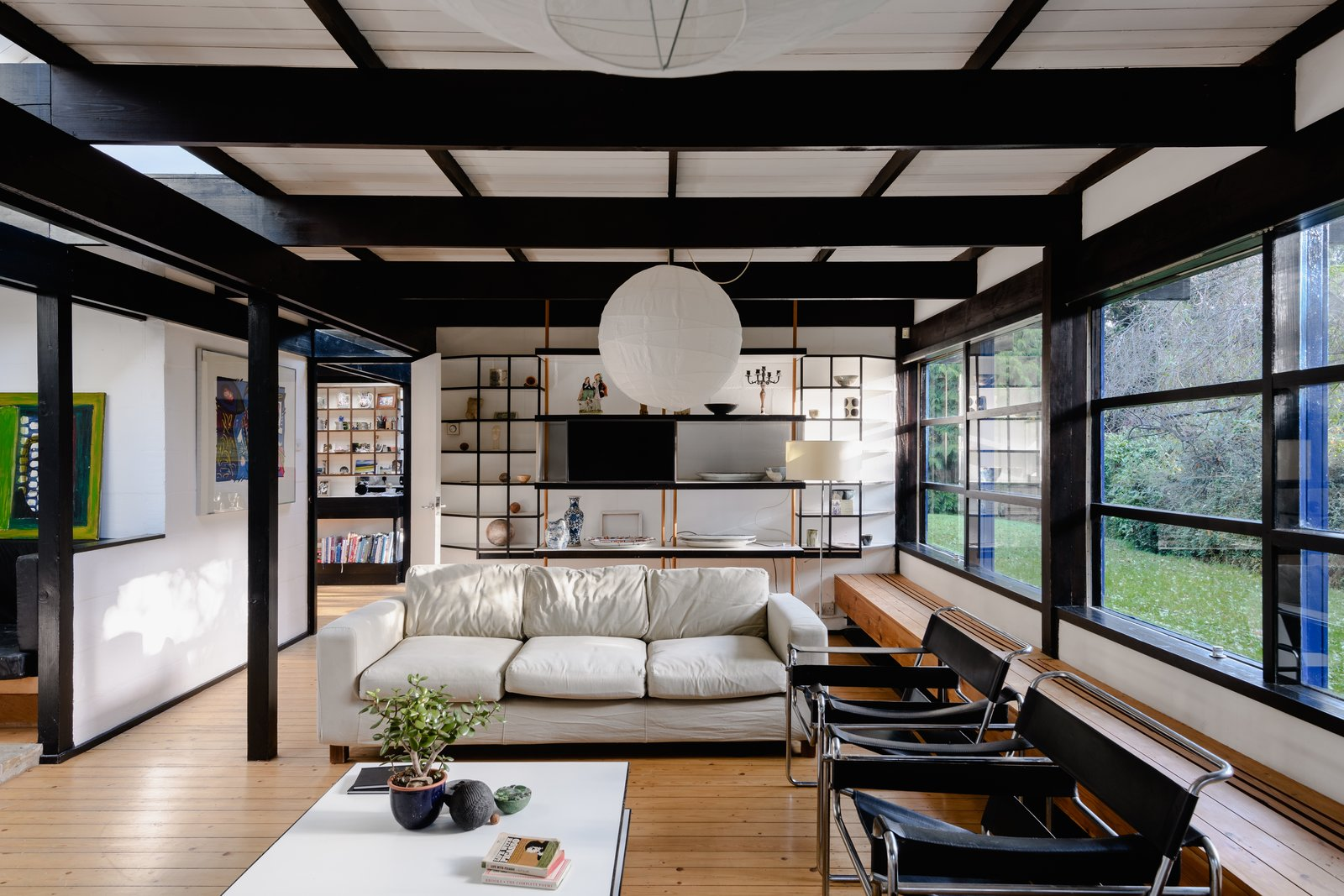 The gallery space also opens into the main living area, where wall-to-wall windows overlook the secluded yard and drench the space in natural light. Furness utilized the post-and-beam design to divide spaces in simple and elegant ways.