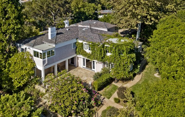 Tucked away in the star-studded neighborhood of Pacific Palisades, the six-bedroom residence is shielded by lush landscaping and mature trees. Ivy covering the facade creates an enhanced sense of privacy.
