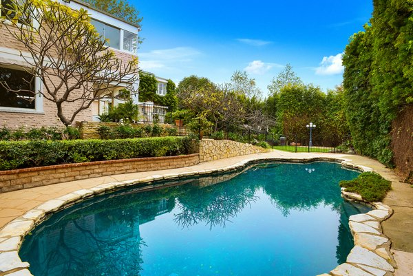 Out back, the in-ground pool is an idyllic spot for entertaining.