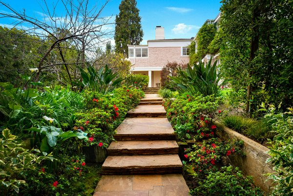 Thriving jungle-like greenery runs along both sides of the main sidewalk leading to the home.
