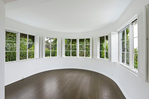 The master bedroom includes a circular sitting room encased in windows. The bright area offers a quiet corner to rest and relax.