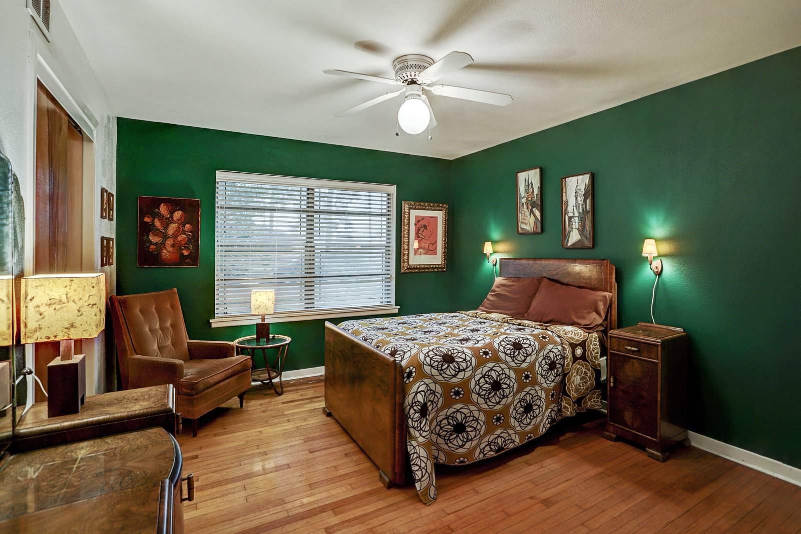 In the master bedroom, richly textured furniture complements the green accent walls.