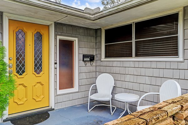 A bright yellow front door offers a warm welcome to residents and visitors alike.