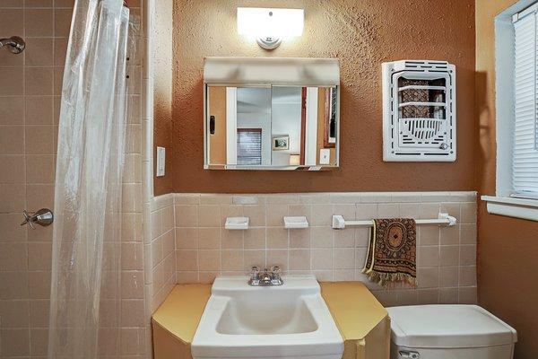 Both bathrooms feature original colored tile.