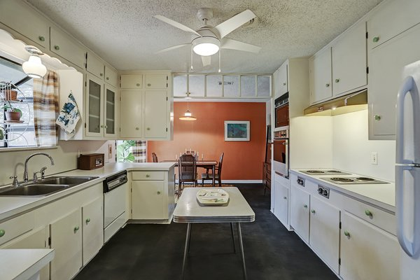 The kitchen comes with original details, including a vintage cooktop and cabinetry. The white palette contrasts with the colorful accent wall in the dining room.
