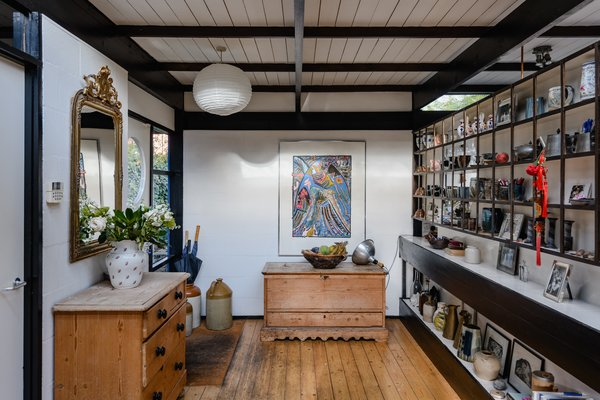 An entrance at the side of the home opens up into a small gallery space, complete with a Japanese-inspired shelving unit for displaying artwork and collectibles.