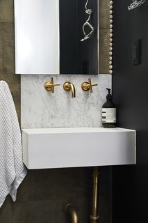 Lawyer-turned-interior designer Delia Kenza recently renovated her parlor floor powder room, which is tucked behind a staircase. She stuck a piece of glass like a transom near the ceiling, exposing the old plaster. She used a textured wallpaper and a marble backsplash alongside brass fixtures and unexpected artwork.