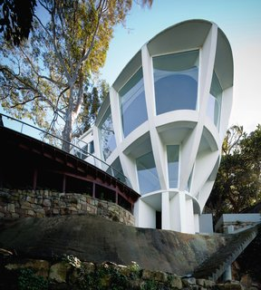 """I like things not to have a beginning and an end,"" says Stan Symonds, an Australian architect obsessed with circular forms and curving walls. Many of his projects feature circular forms of one kind or another, including his Dome House in Seaforth. Just a year after building finishing that project, Symonds completed this striking house nearby for John and Margaret Schuchard that has also been known as the 'Space House' or 'Spaceship.' The building, resembling a lookout station or observation post, sits on a steep hill with panoramic views out across Middle Harbor. The house mushrooms upwards and thrusts outwards at one and the same time, like the rounded bow of a ship emerging from the rock."