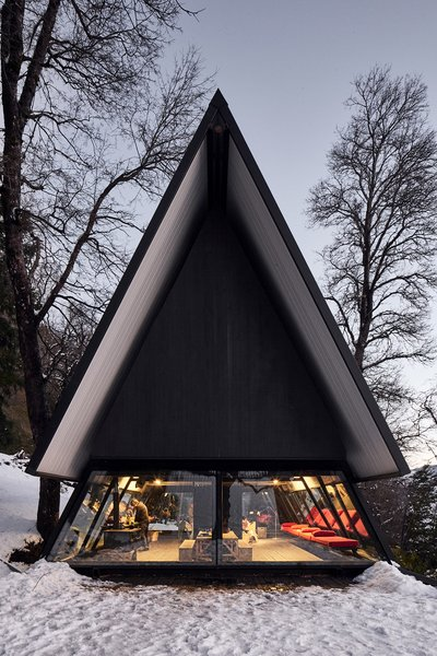 The ground floor of the A-frame structure houses an open-plan dining area.