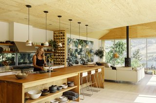 Artist Cori Creed stands in the kitchen of the vacation home in rural British Columbia that she and her husband, Craig Cameron, built with their friend and architect, Kevin Vallely. Cori made the ceramic dinnerware and pendants, while Craig built the kitchen island and installed the plywood ceiling with the help of his stepfather.