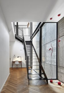 Herringbone floors and a board-formed concrete wall create a linear motif in the second-floor stairwell.