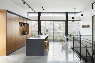 A third-floor kitchen looks out over a balcony garden and city views. Bar stools by Pick Up line the centralized island.