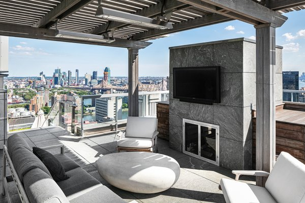 With expansive space and views in every direction, the penthouse's two-story outdoor area offers a private park in the sky. The lower level can be assessed from the living room or master bedroom and features several spots to sit and dine. Here, one of the lounge areas is located on the upper level and can be reached via an outdoor staircase.