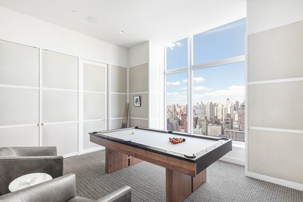 A game room provides another space for entertaining and enjoying views of Manhattan.