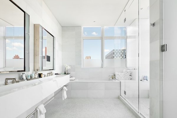 A marble trough sink lines a wall in the bright master bath, complete with an oversized soaking tub and glass walk-in shower.