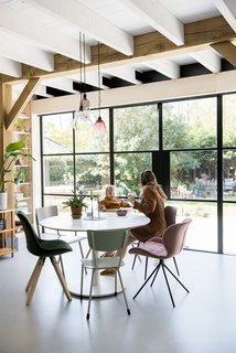 In the dining area, Ayla and the couple's daughter, Cato, sit at an IKEA table surrounded by mismatched chairs. The steel and glass wall is by Different Steel.
