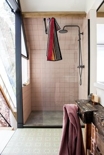 Handmade Portuguese tiles line the floor of the upstairs bathroom, where a MissoniHome towel adds a bright touch.
