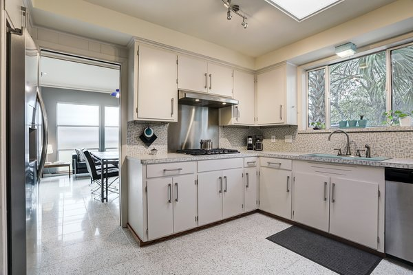 In the vintage-style kitchen, original cabinetry mingles with modern appliances. Terrazzo tiles extend to the adjoining dining and living rooms.