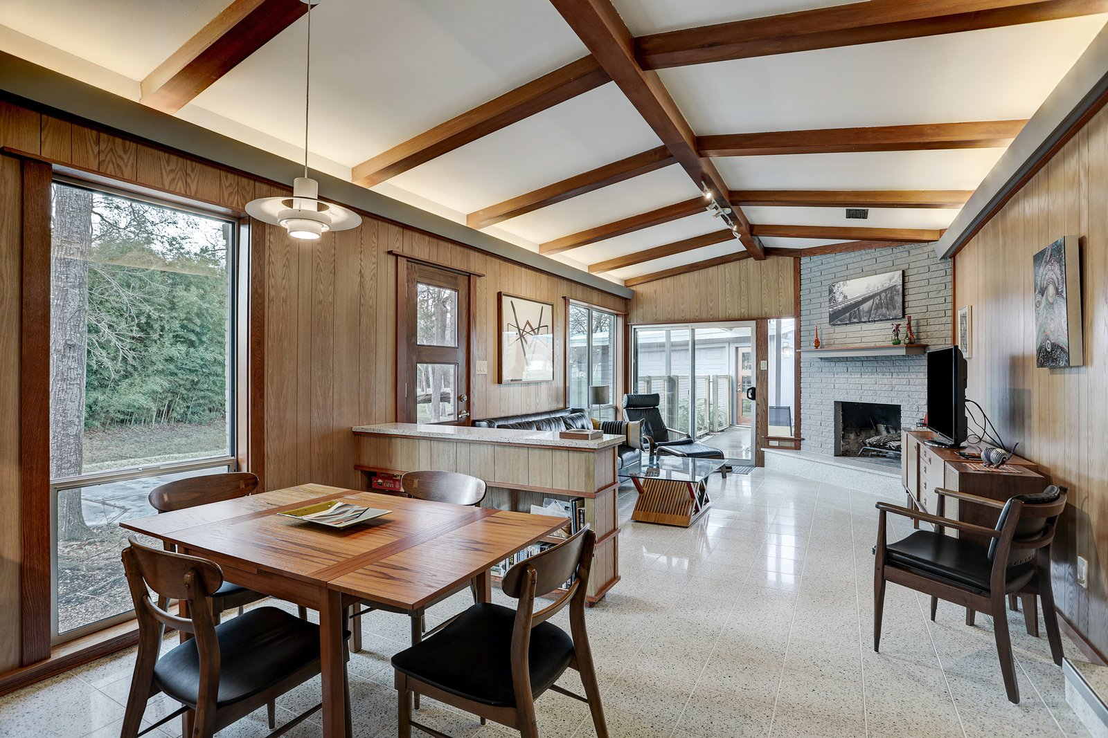 Sporting restored midcentury furniture, the main great room is a time capsule in itself. Wood beams contrast with the crisp white, vaulted ceilings, which provide indirect cove lighting. An original fireplace sits tucked in the corner.