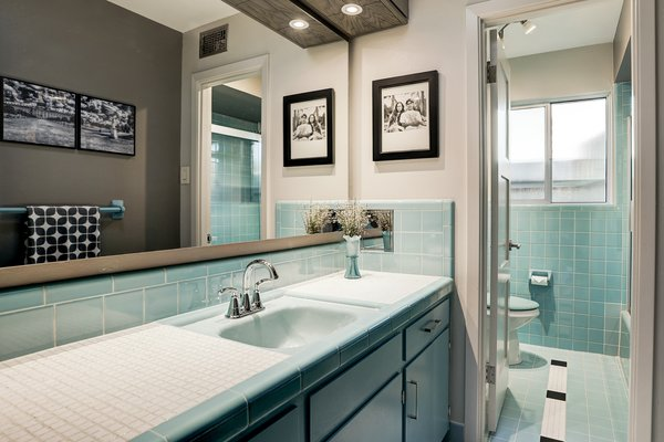 Although updated with new faucets and fixtures, the home's two full bathrooms also feature period details, including vintage colored tiles that run from the sink to shower.